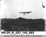 Early Airplane Flying Low Over Field