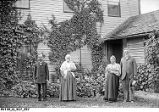 Group of Four Older People Stand Outside an Ivy Covered House
