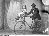 Man Holding a Bicycle With a Little Girl on the Handlebars