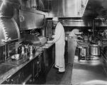Car interior, kitchen, man cooking, Edwin G. Budd Manufacturing Co. photograph (no Bass #)