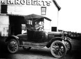 Young man in automobile, W. H. Roberts building in rear (Bass #98415)