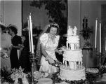 Wedding party, daughter of Nicholas H. Noyes, bride cutting cake, 1938 (Bass # 102455F-10)