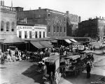 Delaware Street, delivery wagons and crowd at J.L. Keach vegetable market, Corydon Building in background,