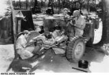 Sergeant George F. Heiny and Others Strip a Weapons Carrier